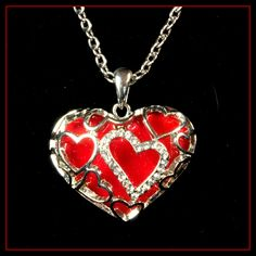 Silver tone, heart necklace with enameled red heart center pendant, adorned with silver tone/ rhinestoned heart cut-outs.