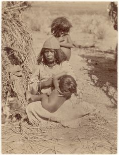 Kaibab Paiute woman nursing a child while another child stands behind her. Woman wears a basketry hat and a fringed and beaded dress. Brush house (?) on the left. 1871-1873