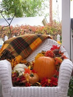 Fall porch display/ autumn leaves / pumpkin / white wicker chair