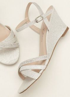 Add a subtle dose of spakle to any ensemble with these rhinestone embellished wedge sandals!  Low wedge sandal features glistening rhinestone embellishments across one of the toe straps.  Heel Height: 2 inches.  Available in Silver Metallic and Nude Metallic.  Available in sizes 5.5-9, 10.  Imported.