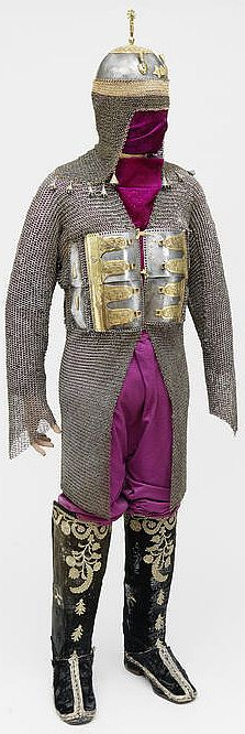 Indian (Deccan) zirah baktar (mail and plate armour shirt) 100 cm long, 17th Century, a long-sleeved mail shirt with seven frontal plates embellished with gilt mounts and four small inscription medallions, the back with five vertical rows of miniature plaques and a pair of Ottoman 19th century embroidered velvet Boots.