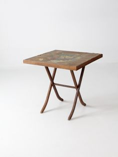 circa 1920s - 1940s A vintage wood folding table. The small card table features…