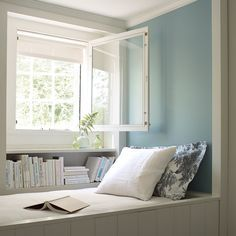 Built-in daybed with light blue wall and open window.