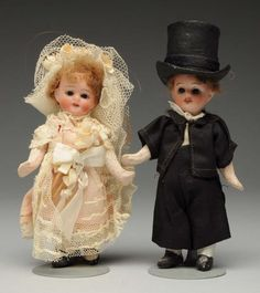 """Rare Goebel Bride & Groom Dolls. Both with bisque socket heads marked with Goebel trademark and mold 120, with glass eyes, open mouths and wigs on mediocre quality papier-mâché bodies with painted shoes and socks; with original bridal outfits. Boy's head needs to be reattached. Darling pair! Condition (Excellent). Size 4 - 1/2"""" T."""
