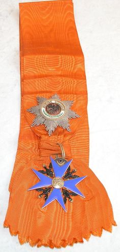 """Prussian Order of the Black Eagle. Set of the Prussian Order of the Black Eagle including breast star, medal and sash. 1.) Enameled silver gilt breast star measures 80mm. Wide pin on reverse exhibits hallmark of """"900"""" and """"835"""" struck over other mark. 2.) Orange watered sash presents enameled silver gilt medal measuring 75mm. Blue enameling on medal exhibits some light abrasions and sash exhibits some minor soiling."""