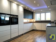 wow kitchen wood floor with white gloss and black glass units