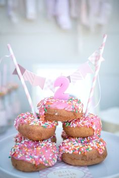 Who needs birthday cake when you can do a celebratory donut tower? This adorable donut-themed 2nd birthday party has all the pink shades and colorful sprinkles a little girl could ever want. With ideas for the decorations, snacks, desserts, signage, and party favors, this inspiring post has lots of little details that look lavish but are easy to accomplish—perfect for your toddler turning two! #birthdaycakes