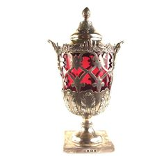 A large Edwardian silver condiment cup with a cranberry glass liner. A large Edwardian silver condiment cup with a cranberry glass liner. In the form of a pedestal urn and cover, the side decorated with floral lattice openwork. Mark of Williams Ltd, Birmingham 1901. 7.9 in (20 cm) height. Weight: 308 grams (without liner).
