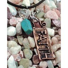This handmade necklace charm necklace with 'Faith' on a copper tone charm and 2 smaller charms, one is a cross and the other is a faux turquoiuse. The word faith is raised and antique detailing around