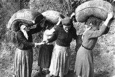 Donne con sacchi di grano sulla testa
