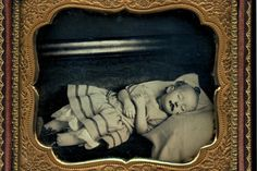 A framed black-and-white image of a deceased infant