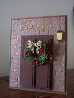 SueBee Cards  Susan Bagley  Christmas Door wishing you Blessings.  Sizzix brick EF, Punch bunch pine branch MINI, hand  made door and knob, light made from small price tag punch,mini flower punch, glossed with glossy accents, stickles, wired ribbon.