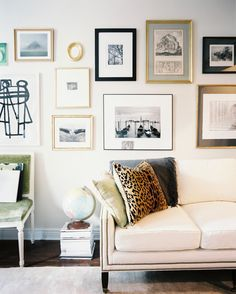 Living Room Traditional- gallery wall of art hung above a white couch and a green side chair love punch of leopard
