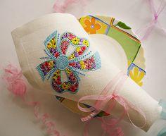 """Вышитая салфетка """"Бантик""""выполнена из льна белого цвета, украшена машинной вышивкой высококачественными полиэстровыми нитками немецких производителей.  Яркий, веселый узор этих салфеток украсит любой праздничный стол. Такой столовый текстиль послужит прекрасным подарком на день рождения, новоселье, свадьбу, 8 марта, будет радовать своих владельцев долгие годы."""
