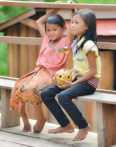 2 school girls with a ball on a fence Dor Village Cambodia