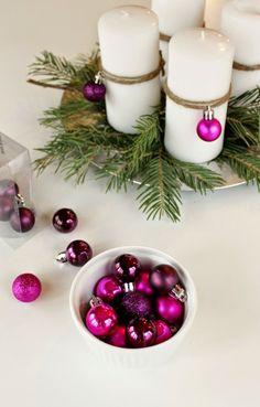 Die Adventskranz-Kerzen können Sie mit kleinen Christbaum-Kugeln dekorieren