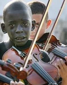 5. Diego Frazão Torquato, 12 year old Brazilian playing the violin at his teacher's funeral. The teacher had helped him escape poverty and violence through music