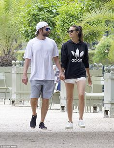 Loved up: On the streets with Bradley the model opted for a casual look and dressed down in a black Adidas hooded top and a pair of short white shorts