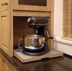 Doors don't always have to go out; they can go up too. The ultimate in innovation is right here: a slide-out shelf behind a pull-up cabinet door. (Click the photo to see the full image.) Keep unsightly small appliances (blender, mixer) stashed neatly but still accessible.