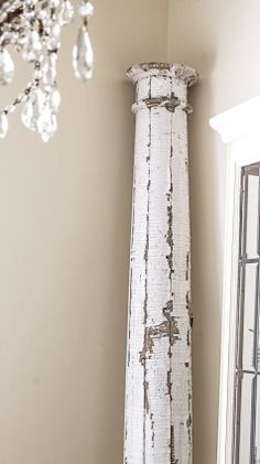 Love the chippy wood post in a room with a glass chandelier White Lace Cottage