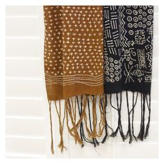 Malian artisans add visual interest to gossamer thin cotton scarves with an updated mudcloth, also known as bogolan, dyeing process. Available in rust and black. The black dye contrasts boldly with the undyed white patterns, and with the long fringe, the scarf allows you to incorporate African mudcloth into your ensemble without the bulk and weight of the traditional textile.