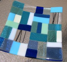 Beautiful fused glass plate with a modern mosaic design in ocean beach colors of blue, turquoise, French vanilla, aqua blue, mint green, white, blue and black streamers, on a clear background. This plate has an additional layer of clear glass on the back for a more elegant look and for