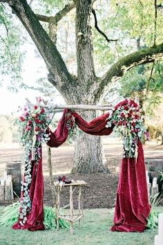 deep red velvet draped wedding arch / http://www.deerpearlflowers.com/wedding-ceremony-arches-and-altars/5/