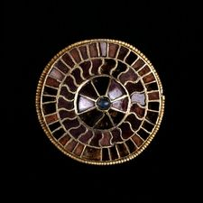 Gold Disc Brooch  Merovingian, late 6th century AD  Probably from Germany    Inlaid with garnets and a blue glass stud