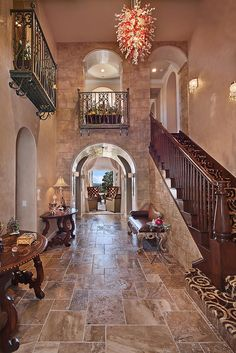 The Mediterranean styling of this luxury foyer is as unmistakable as it is beautiful. Don't you just love that balcony in the back?