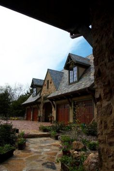 Stone garage with dormers and natural wood doors