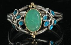 Jessie M. King for Liberty & Co. Arts and Crafts ring. Silver, gold, enamel and chrysoprase. H: 1.2 cm (0.47 in). British, c. 1900. Sold by Tadema Gallery. View 1.