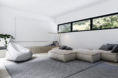 Another seating area is a bit warmer with a modern sueded bean bag chair and seating cushions that evoke the cozy macrame of your grandmother's house.