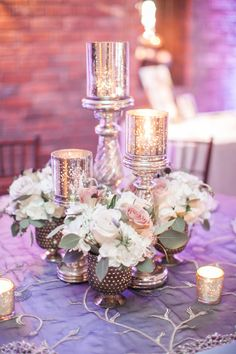 Wedding Centerpiece Our set of 3 silver mercury glass candle holders, wood resin and mercury vases, floral of ivory hydrangea, lavender, Earl Grey roses, Amnesia roses and plum scabiosa. Our slate mum overlay.