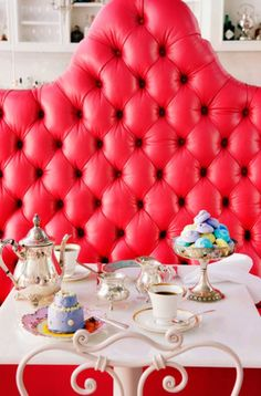 Tufted red leather gives this over-sized banquette a boost. Accompanied by bistro chairs and table, this lovely setting would go well in a retro kitchen.
