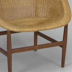 Wicker chair in bowl shape with teak legs and cross bar.