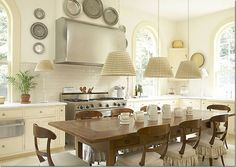 Love the all white/cream kitchen and good idea for dining table in kitchen jck