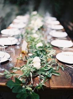 An example of elegant on a budget - wooden tables, affordable eucalyptus leaf runner