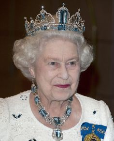 Choosing an icy blue and diamond tiara for her hosting role of a banquet for Commonwealth leaders in Perth, 2011, Queen Elizabeth keeps her look chic and simple in an elegant white lace dress littered with blue crystal petals.