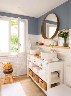 00426636. Baño con mueble bajolavabo en blanco, espejo redondo y pared pintada de azul 00426636