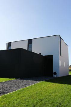 Woning met in het zicht blijvend glad industrieel beton en zwart aluminium.