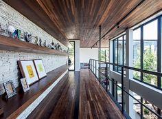 A estrutura metálica recebeu assoalho de cumaru, da Madeireira Monte Sinai. A mesma madeira foi usada no forro e nas prateleiras, fixadas na parede revestida com canjiquinha de pedras (Foto: Xico Diniz/Divulgação)