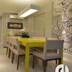 Projeto RL Arquitetos. Mesa amarela, com poltronas e papel de parede, lustre de centro, buffet com quadro.