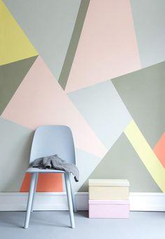 Une déco pastel et géométrique : le mur galerie d'art, Réinventez la peinture murale avec de grands aplats géométriques. Comment faire ? Tracez des triangles géants sur un mur en vous inspirant de la photo. Utilisez un tasseau en guise de règle. Délimitez un triangle avec du ruban de masquage. Peignez l'intérieur. Laissez sécher avant d'enlever l'adhésif et de passer à la forme suivante.