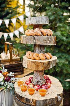 Zeigen Sie herrlich saisonale Donuts und Apfelwein auf einem Holzblockhalter.