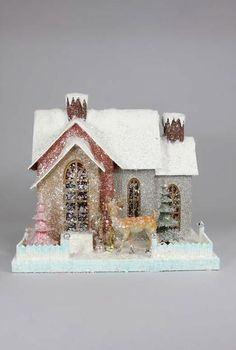 Pressed paper putz house with bottle brush trees,deer, glitter, and mica accents.