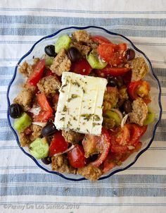 Food in Greece by Penny De Los Santos - cretan rusks, tomatoes, onions, olives, cucumbers, feta, oregano & olive oil, of course!