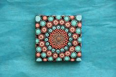 This is an original hand painted mandala that was done with acrylic paint on canvas. Sealed with a clear satin finish. The colors include bright corals and turquoise. There are metallic blue and rose gold dots as well. The canvas is 3 x 3 and is on a wood frame. This beautiful
