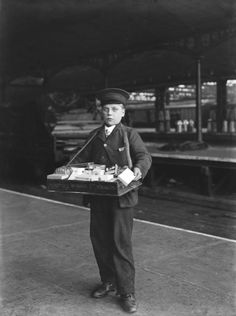 A boy working for Wymans & Sons selling tobacco at Euston station, London, 1908. Passengers could buy tobacco, cigars or cigarettes on the platform as well as in station kiosks. At first smoking was banned on the railways but in 1868 an act was passed permitting smoking in carriages. At least one railway carriage of each class was a smoking carriage. These were marked on the outside with an S.