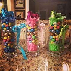 """Grown Up """"Easter Basket,"""" great Spring party favors for adults. I bought a package of beer steins at Target for $9.99, but you could probably get some at the Dollar Store. Add a little Easter grass at the bottom, layer various Easter candies, top with a little more grass and a Lindt chick (you could even use a Peep chick). Then, tie a ribbon bow on the handle."""