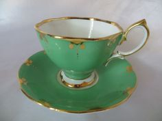 "PATTERN: SOLID GREEN OUTTER COLOR WITH GOLD MIDAS RIM - SOLID INNER WHITE. SIZE:CUP 2 3/4"" HIGH - SAUCER 5 1/2"" HIGH. MADE BY: ROYAL ALBERT - MADE IN ENGLAND. 